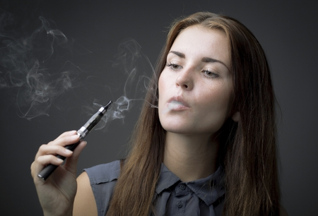 Elegant woman smoking e-cigarette with smoke portrait photo