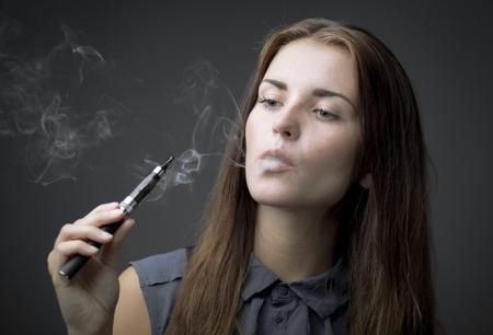 Mujer elegante de fumar cigarrillo electrónico con el retrato de humo