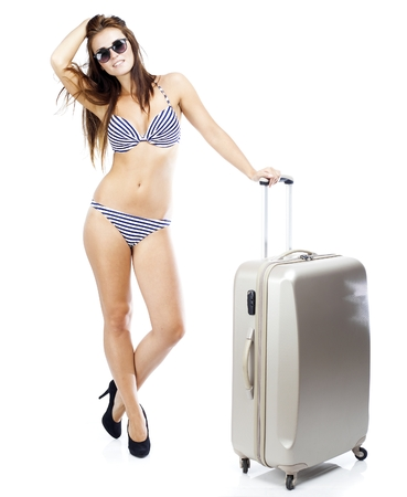 Tourist woman in bikini with travel suitcase isolated white photo