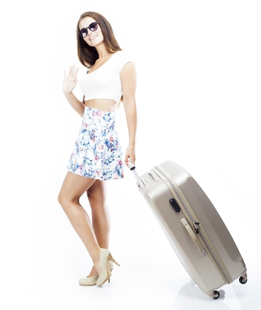 Tourist woman with suitcase waving hand isolated white photo