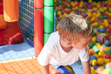 playcentre: Little boy playing in colorful balls park playground Stock Photo