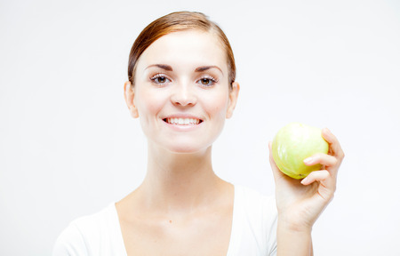 dentition: Smiling young woman holding and eating green apple, Healthy teeth concept