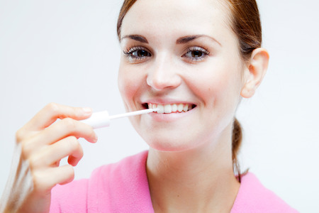 Teeth whitening, woman holding brush and cleaning teeth photo