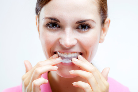 Teeth whitening, woman with tooth tray on teeth