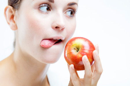 Young woman holding and eating red apple, Healthy teeth concept photo