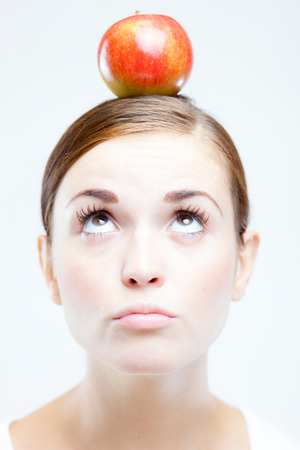 Young woman with red apple on her head photo