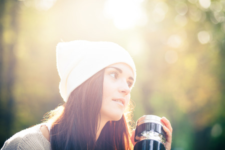 Young woman with bottle outdoor portrait in soft sunny daylight photo