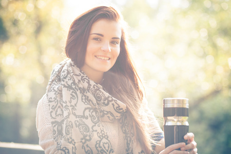 Young woman with thermos outdoor portrait in soft sunny daylight photo