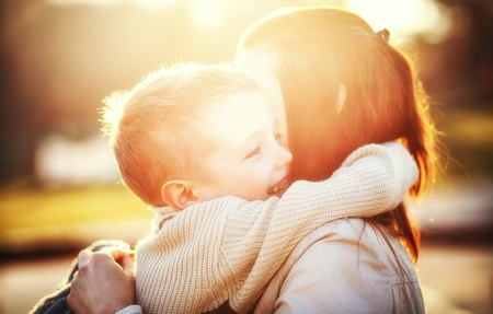 Madre que abraza a su druing niño a caminar en el parque