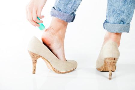 Woman in high heels using cosmetics for foot heel