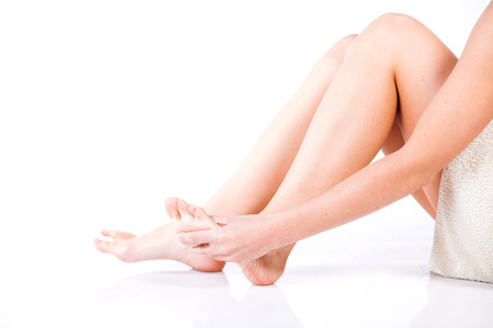 Woman massaging her aching foot, female problem concept photo