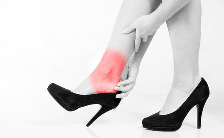 Dolor de piernas en el tobillo de la mujer en tacones altos Foto de archivo