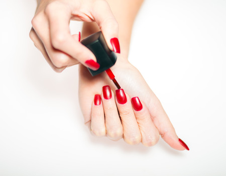 Red manicure nail polish, painting nails on bright background Banque d'images