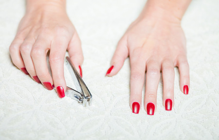 clipper: Woman hand manicure with nail clipper Stock Photo