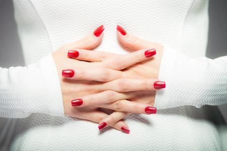 Vrouw toont haar rode nagels, manicure-concept