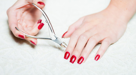 Woman hand manicure, trimming cuticles photo