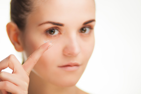 nearsighted: Woman with contact lens on finger, healthcare concept