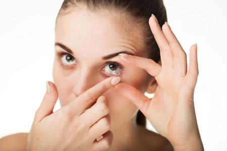 lentes de contacto: Mujer que pone la lente de contacto en su ojo concepto de la asistencia sanitaria Foto de archivo