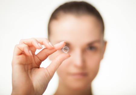 Donna con la lente a contatto sul dito, concetto di assistenza sanitaria