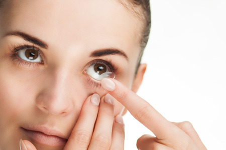 Woman putting contact lens in her eye concept of healthcare Foto de archivo