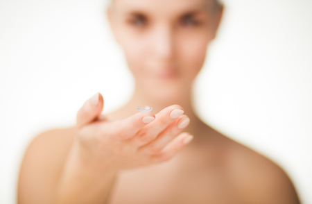 shortsighted: Woman with contact lens on finger, healthcare concept