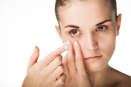 shortsighted: Woman putting contact lens in her eye concept of healthcare Stock Photo