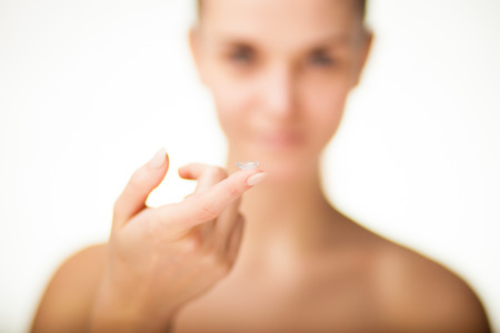 wearer: Woman with contact lens on finger, healthcare concept