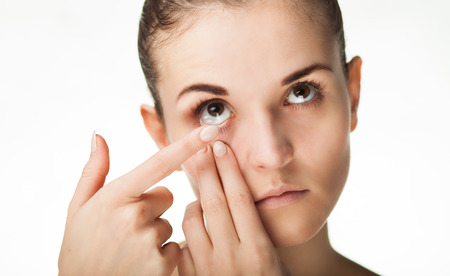 wearer: Woman putting contact lens in her eye concept of healthcare Stock Photo