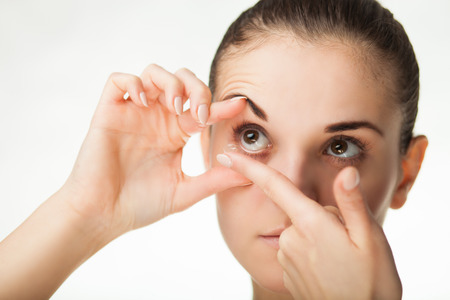 Woman putting contact lens in her eye concept of healthcare Stock Photo