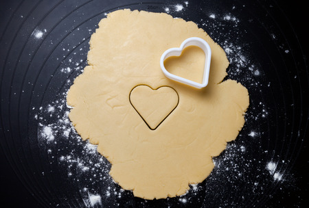 cookie cutter: Heart shaped cookie cutter on dough preparing cookies concept