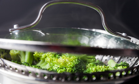skimmer: Freshly steamed green broccoli in skimmer pot with steam Stock Photo