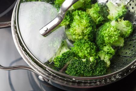 Freshly steamed green broccoli in skimmer pot preparing vegetables concept Standard-Bild