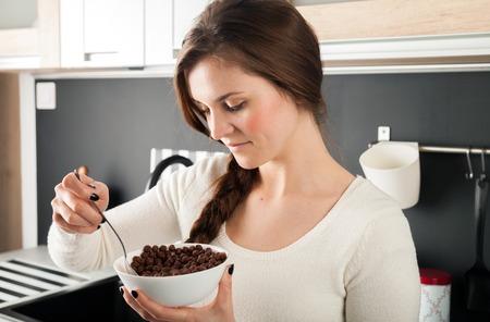 comiendo cereal: Mujer con plato de cereal de coco en la cocina moderna Foto de archivo