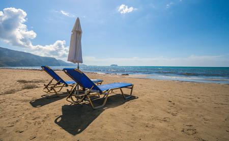 sun umbrella: Empty lounge chairs with sun umbrella on a sandy beach