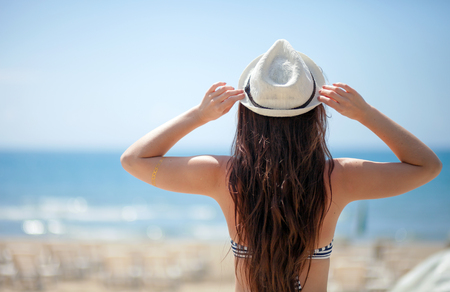 sunstroke: Woman in hat on beach looking at the sea during summer vacation Stock Photo