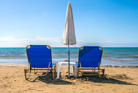 lounge chairs: Empty lounge chairs with sun umbrella on a sandy beach