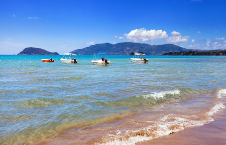 motorboats: Motorboats on blue sea near to the sandy beach in hot summer day