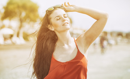 sunstroke: Happy young woman on the beach in hot summer sun light Stock Photo