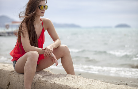 sunstroke: Young woman sitting on the beach during summer vacation Stock Photo