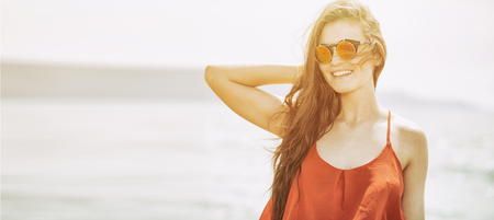 Happy young woman on the beach in hot summer sun light Stock Photo