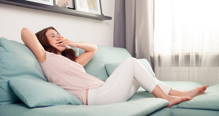 Sleepy young woman lying on couch and relaxing at home, casual style indoor shoot