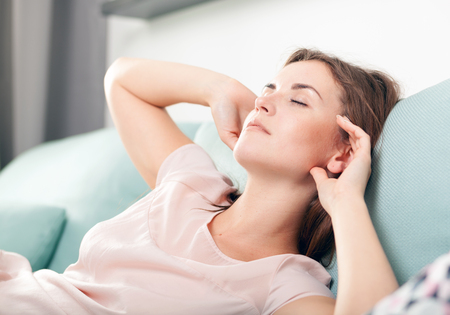 wellness sleepy: Sleepy young woman lying on couch and relaxing at home, casual style indoor shoot