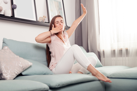 dozing: Sleepy young woman lying on couch and relaxing at home, casual style indoor shoot