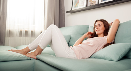 dozing: Happy young woman lying on couch and relaxing at home, casual style indoor shoot Stock Photo