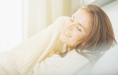 Happy young woman lying on couch and relaxing at home, casual style indoor shoot Stock Photo