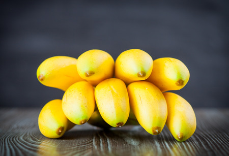 ingradient: Bunch of bananas on wooden table dark background, front view Stock Photo
