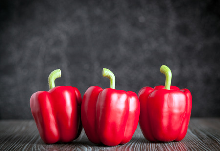 ingradient: Red bell pepper on wooden board dark background, front view