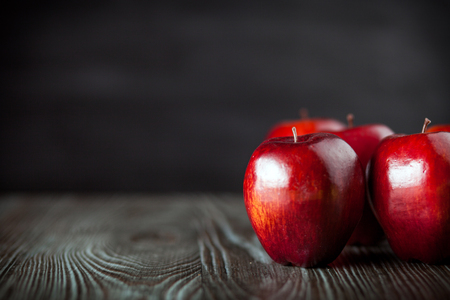ingradient: Red apples on wooden table dark background, copy space