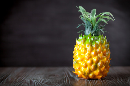 ingradient: Fake pineapple on wooden board dark background, copy space