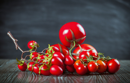ingradient: Various tomatoes on wooden table dark background, front view